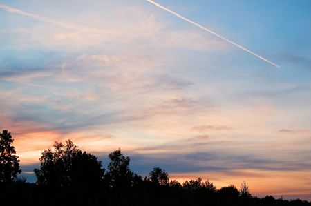 reveille: A beautiful sunrise, clouds, painted in red, orange colors, the trees in the meadow, the trail from an airplane in the sky