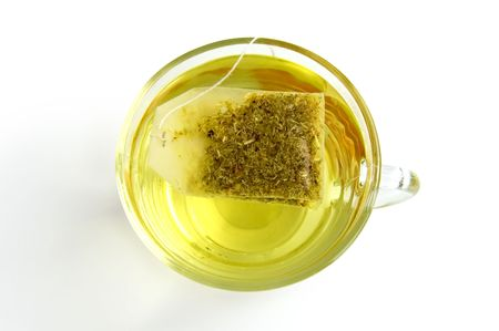 The bag of green herbal tea in a glass bowl with water, isolated on a white background