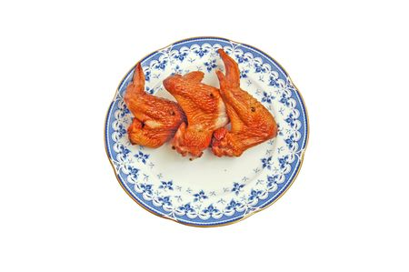 Smoked chicken wings on a porcelain plate with a blue pattern on a white background photo