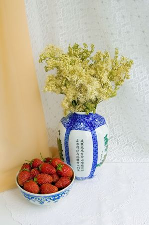 A cup of strawberries, a vase of wild flowers on the table with a white cloth on a background of beige and white shades photo