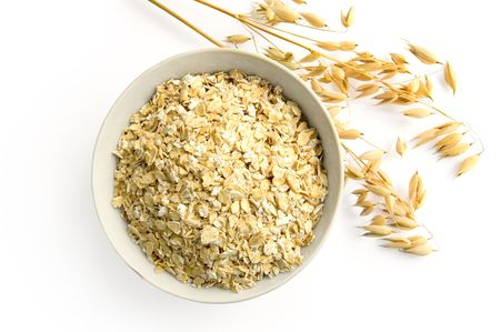 Rolled oats in a bowl, ripe stalks of oats isolated on a white background