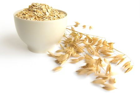 Oat flakes in a tea cup, ripe stalks of oats isolated on a white background