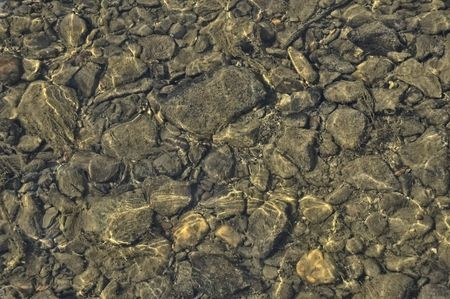 shallow water: The texture of the large and small stones on the river bottom and the reflection on the water surface Stock Photo