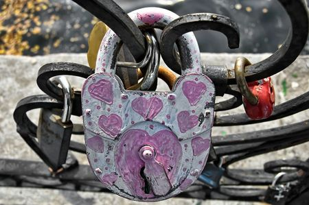 White with painted pink serrdechkami padlock close to the fence on the background of other castles, water, concrete fences photo