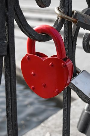 Red padlock on a heart-shaped close-up on the fence on the background of other castles, water, concrete fences photo