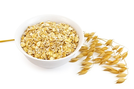 Rolled oats in a bowl, the stem of ripe oats is isolated on a white background photo