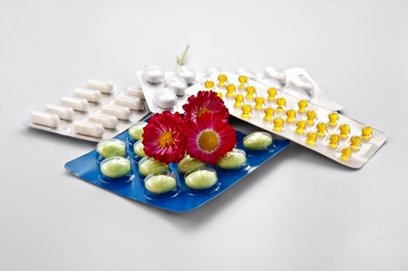 White and green tablets, yellow capsules in packs with three daisies isolated on gray background Stock Photo - 9250587