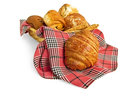 Buns, bread sticks in a wicker basket and a croissant separately on the red checkered napkin isolated on a white background photo