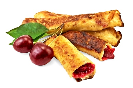 Pancakes with cherry filling, two cherries with green leaves isolated on white background photo