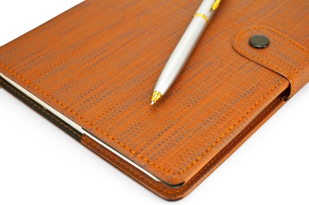 Brown notebook with a silver pen isolated on white background photo