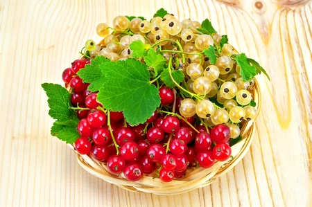 mellow: Sprigs of red and white currants with green leaves in a wicker tray on a light wooden board Stock Photo