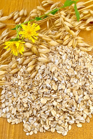 wild oats: Oat flakes with yellow wild flowers and stems of oats on a wooden board