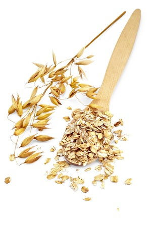 Rolled oats in a wooden spoon, stalks of oats is isolated on a white background photo
