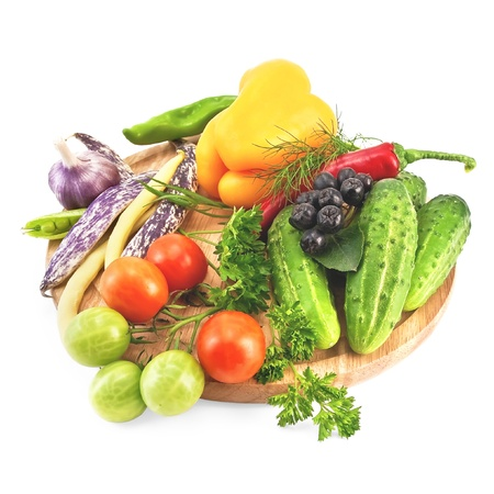 Tomatoes, cucumbers, sweet and hot peppers, pea pods, three pods of beans, garlic, parsley, dill, tarragon and brush Aronia on a wooden circular board isolated on white background photo