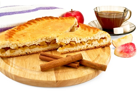 Apple pie with cinnamon sticks on a wooden round board, a whole apple, napkin, tea in the brown cup with two pieces of sugar, two slices of apple isolated on a white background photo