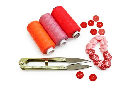 Three spools of thread of orange, red and pink, small metal scissors, red and pink buttons with a pattern isolated on white background photo