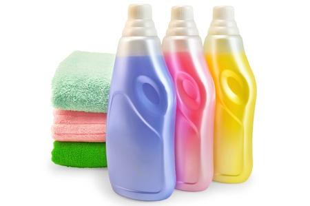 dry cleaned: Tre bottiglie di ammorbidente rosa, giallo e lilla, tre asciugamani isolato su sfondo bianco Archivio Fotografico