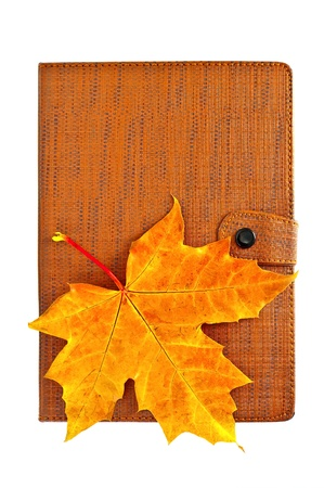 Closed notebook with red and yellow maple leaf isolated on white background photo