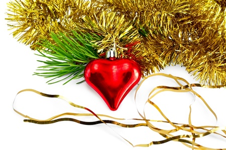 Christmas decorations in the form of a red heart, a branch of pine, gold tinsel isolated on white background Stock Photo - 11437599