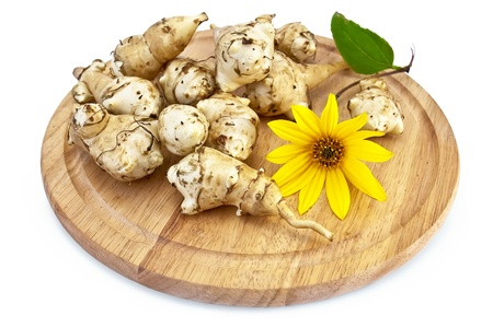 Tubers of Jerusalem artichoke with a yellow flower on a round wooden board isolated on white background