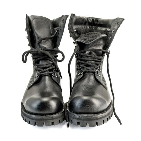 botas: Un par de botas altas de cuero negro sobre fondo blanco