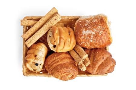 canasta de panes: Bollos con pasas, palitos de pan, croissants, puff bollo con arena en una cesta de mimbre aisladas sobre fondo blanco