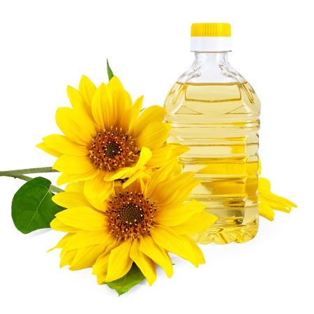 Vegetable oil in a bottle with three flowers sunflower isolated on a white background photo