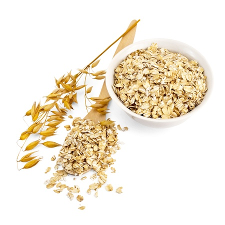 Rolled oats in a wooden spoon and a white porcelain bowl, oat stalks isolated on white background Stock Photo