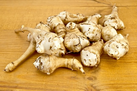Lots of tubers of Jerusalem artichoke on a wooden board photo
