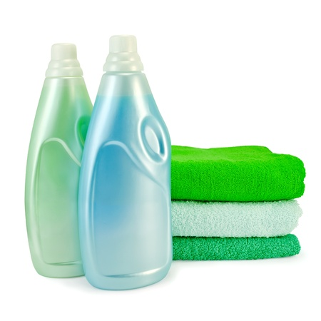 Two bottles of fabric softener blue and green colors, a stack of three towel isolated on white background