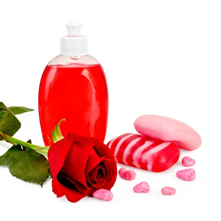Red liquid soap in a bottle, solid striped red and pink soap, bath salt, red rose isolated on white background photo