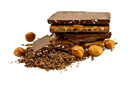 A stack of different chocolates, lots of grated chocolate with two slices of chocolate with nuts, five nut kernels hazelnuts isolated on a white background photo