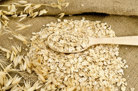 Oat flakes with a wooden spoon, stalks of oats on sacking and wooden board photo