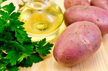 Four red potatoes, a bunch of parsley, vegetable oil in a bottle on the background of wooden boards photo