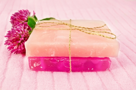 Two homemade pink soap, tied with hemp rope, two flowers pink clover on the terry towel photo