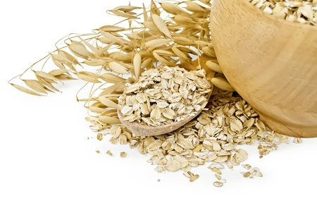 Oat flakes in a wooden bowl and spoon, stalks of oats isolated on white background