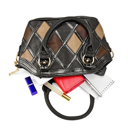Open ladies leather handbag, red purse, perfume, lipstick, phone, notebook, pen, electronic book isolated on white background photo
