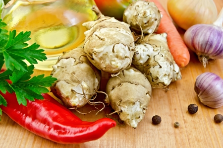 Five tubers of Jerusalem artichoke, garlic, onion, carrot, parsley, red pepper, peas sweet pepper and a bottle of vegetable oil on a wooden board photo