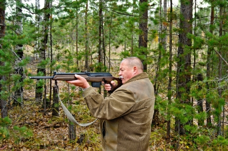 An older man in a brown jacket with a rifle in his hands on a background of trees photo