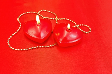 Two red candles in the shape of a heart with golden decorations on a red silk photo