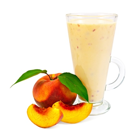Milkshake in a glass beaker with peaches and green leaves it is isolated on a white background