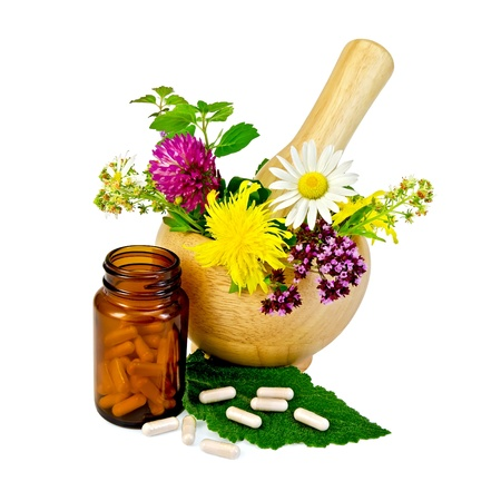 Capsules on green leaf of sage, brown jar, wooden mortar with a sprig of mint, flowers of chamomile, clover, oregano, mignonette, elecampane isolated on white background photo