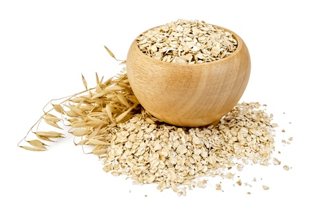 Oat flakes in a wooden bowl, stalks of oats, oat flakes scattered on the table isolated on white background