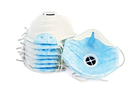 A stack of white and one detached disposable respirators with blue detail isolated on white background photo