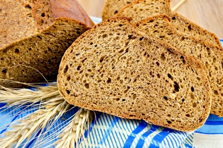 A few slices of rye bread, three rye spikelets on a blue napkin against a wooden board Stock Photo - 17361164