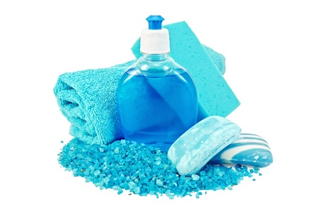 solid blue background: Blue liquid soap in a bottle, solid blue striped and mottled soap, bath salt, blue towel and sponge isolated on white background