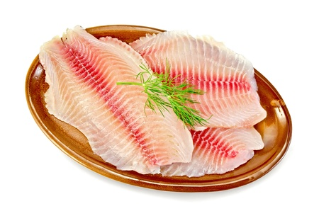 Tilapia fillets with dill in a pottery plate isolated on white background photo