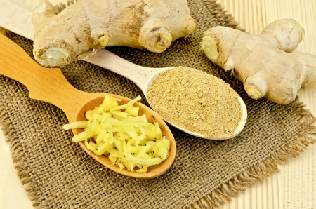 Two wooden spoons of powder and grated ginger, ginger root on a napkin on a burlap background wooden board