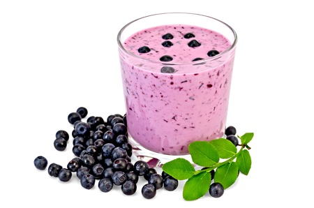 The glass of milkshake and blueberries, berries and green sprig of blueberries isolated on white background Stock Photo