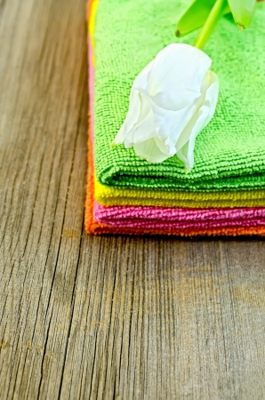 terry: A stack of towels green, pink, orange and yellow with white tulip on an old wooden board